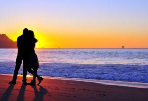 夕暮れの海辺で抱き合う男女