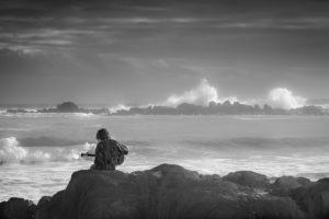 一人で海で歌う男